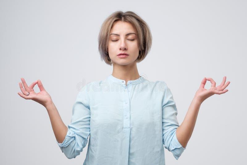 Het jonge vrouw mediteren, houdend haar dient yogagebaar in, voelend kalm en positief royalty-vrije stock afbeeldingen
