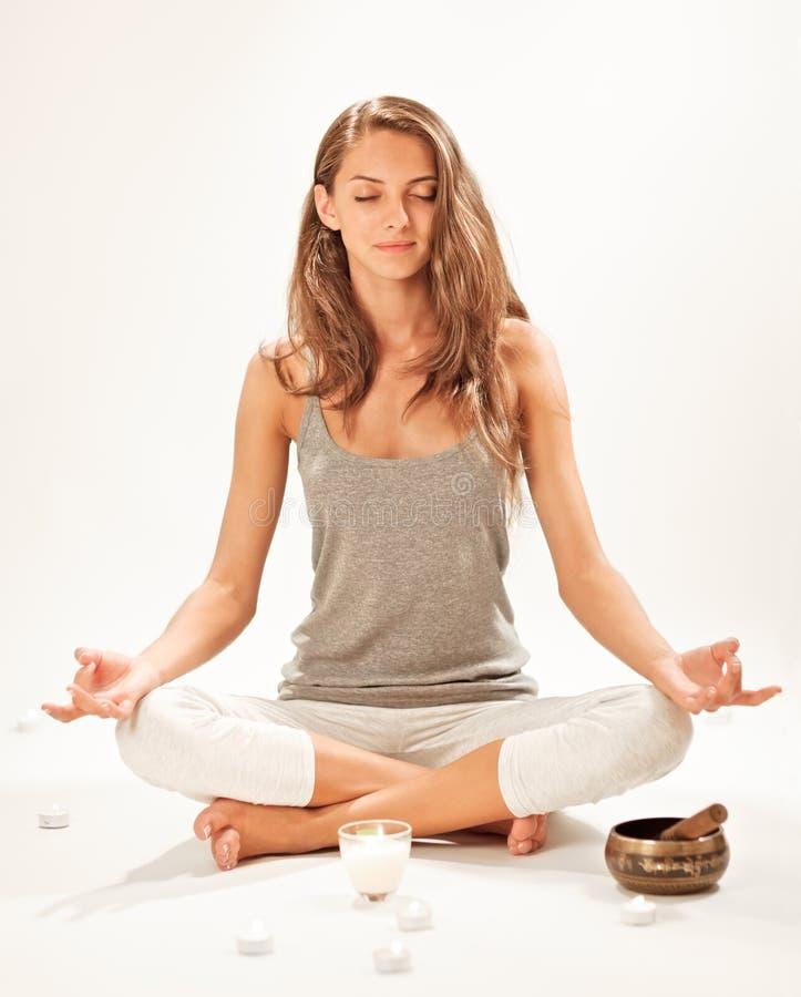 Het jonge vrouw mediteren in lotusbloem stelt stock afbeelding