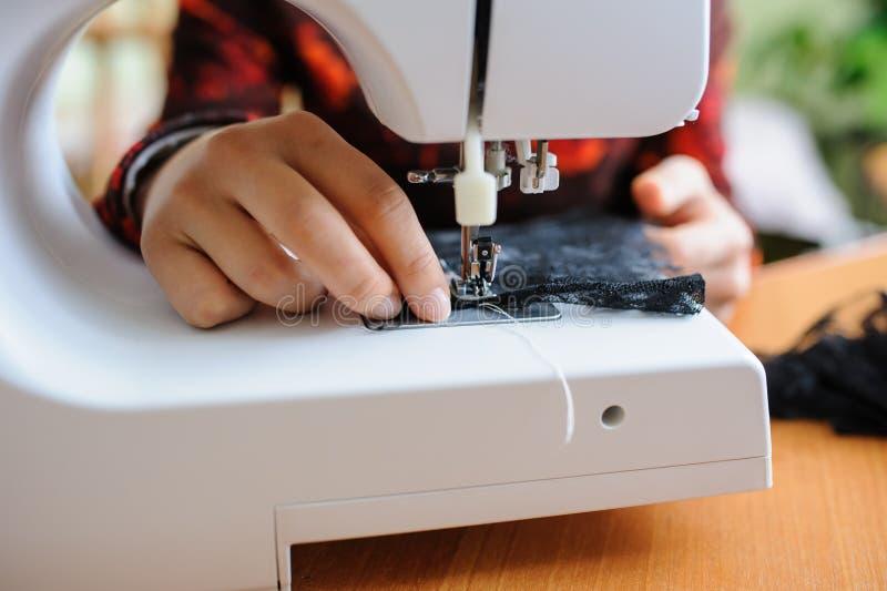 Het jonge vrouw naaien met naaimachine stock foto's
