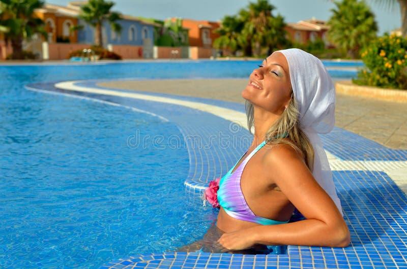 Het jonge vrouw ontspannen bij de pool stock foto's
