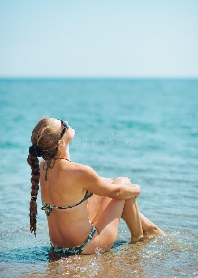 Het jonge vrouw ontspannen bij kust. achter mening stock foto