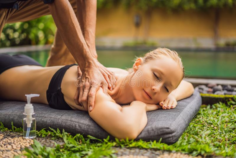 Het jonge vrouw ontspannen buiten bij een gezondheidskuuroord door een zwembad terwijl het hebben van een massage royalty-vrije stock foto's