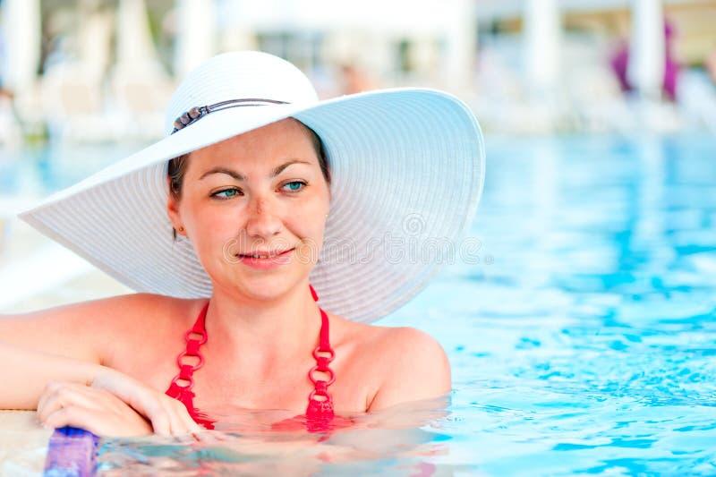Het jonge vrouw ontspannen in de pool stock afbeelding