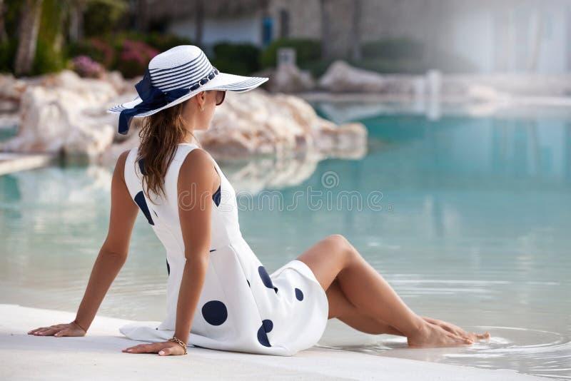 Het jonge vrouw ontspannen door de pool royalty-vrije stock afbeelding