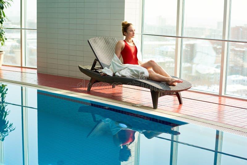Het jonge vrouw ontspannen door zwembad stock foto's