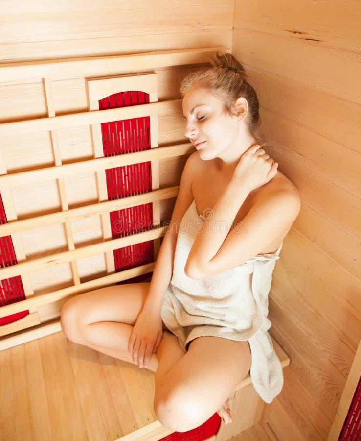 Het jonge vrouw ontspannen in een sauna stock fotografie