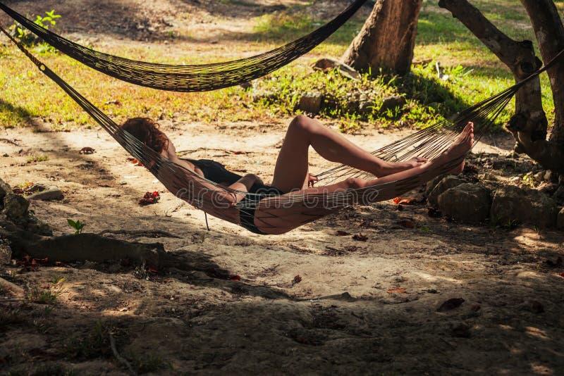 Het jonge vrouw ontspannen in hangmat stock fotografie