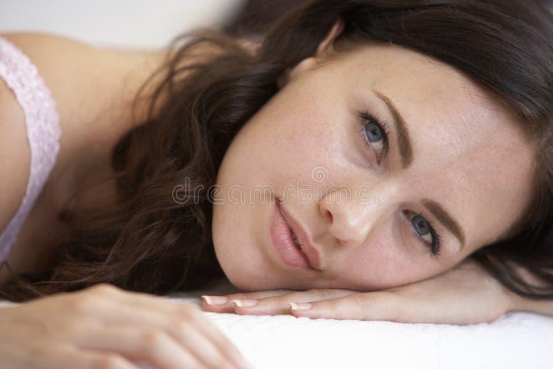 Het jonge vrouw ontspannen op bed royalty-vrije stock foto