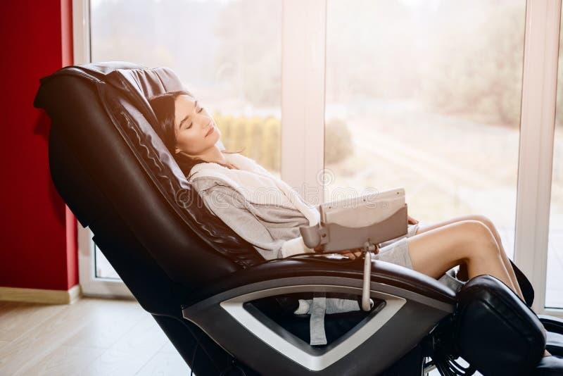 Het jonge vrouw ontspannen op de het masseren stoel stock afbeelding