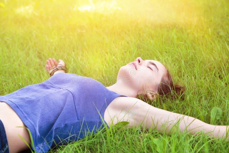 Het jonge vrouw ontspannen op een weide stock afbeelding