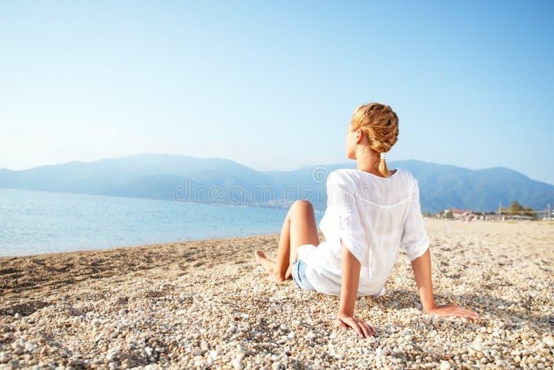 Het jonge vrouw ontspannen op het strand in de ochtend stock fotografie
