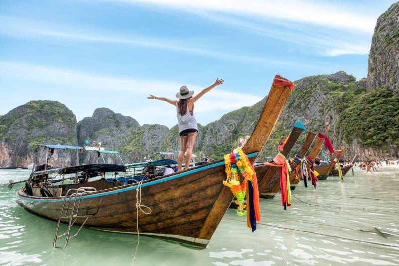Het jonge vrouw ontspannen op houten lange staartboot stock afbeeldingen