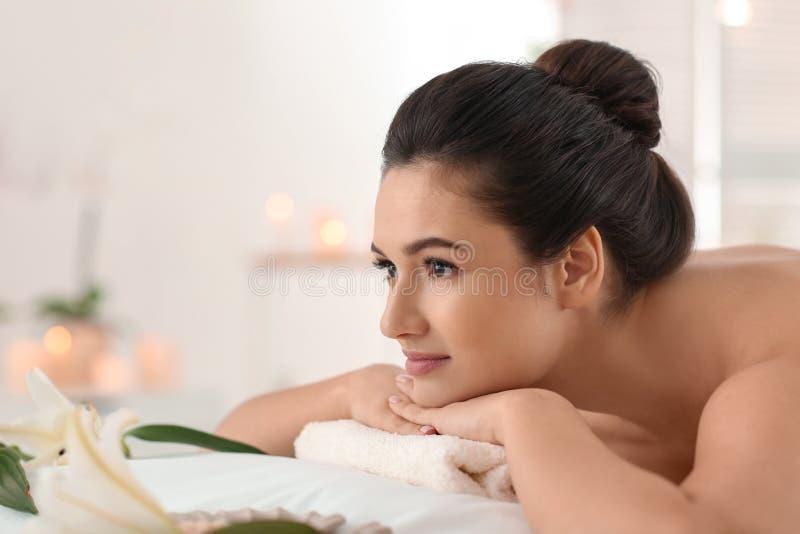 het jonge vrouw ontspannen op massagelijst bij kuuroordsalon royalty-vrije stock afbeeldingen