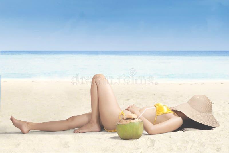 Het jonge vrouw ontspannen op strand met hoed stock afbeelding