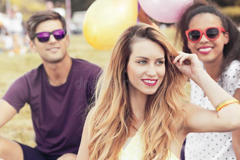 Het jonge vrouw ontspannen in openlucht met vrienden royalty-vrije stock fotografie