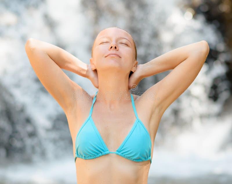 Het jonge vrouw ontspannen in waterval royalty-vrije stock foto's