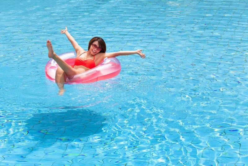 Het jonge vrouw ontspannen in zwembad royalty-vrije stock foto