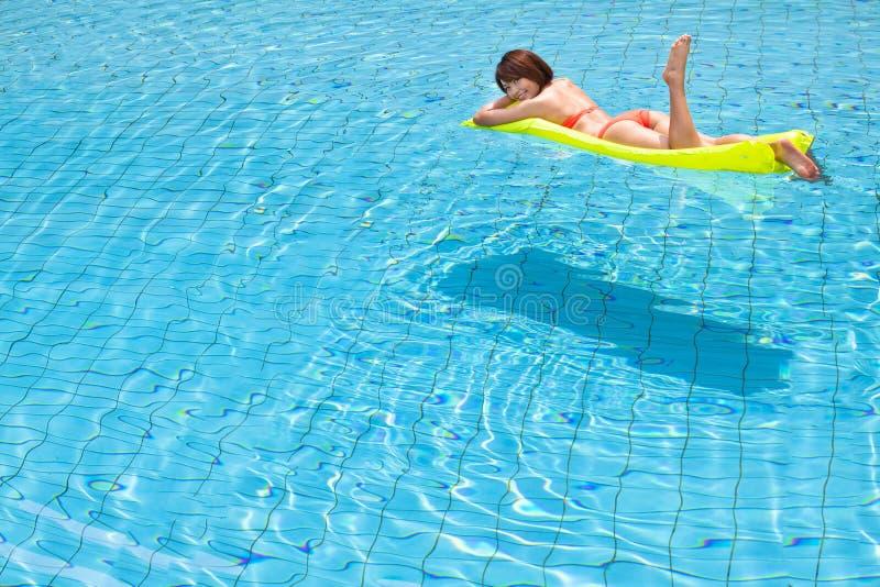 Het jonge vrouw ontspannen in zwembad stock foto