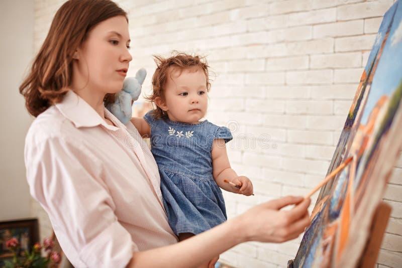 Het jonge Vrouw Schilderen met Kind in Art Studio royalty-vrije stock foto