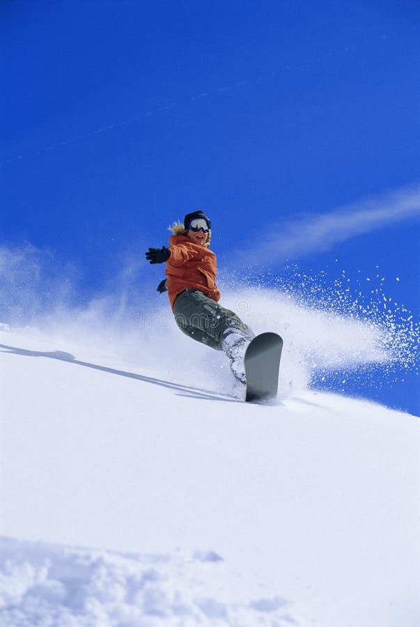 Het jonge vrouw snowboarding stock foto