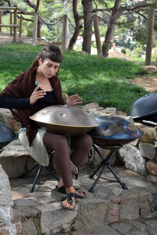 Het jonge vrouw spelen hangt instrument