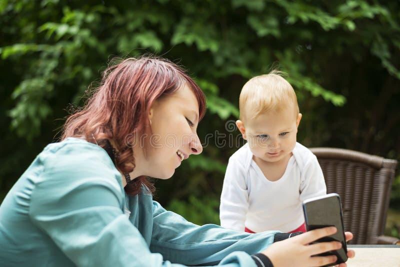 Het jonge vrouw spelen met haar baby, die iets op haar telefoon tonen royalty-vrije stock fotografie