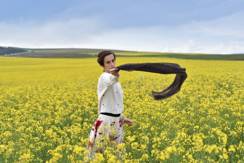 Het jonge vrouw spelen met sjaal op een canolagebied stock afbeelding