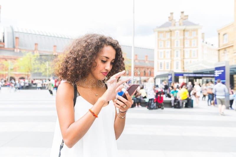 Het jonge vrouw spelen met vergroot werkelijkheidsspel in Londen royalty-vrije stock foto's