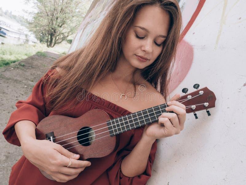 Het jonge vrouw spelen op Ukelele stock foto