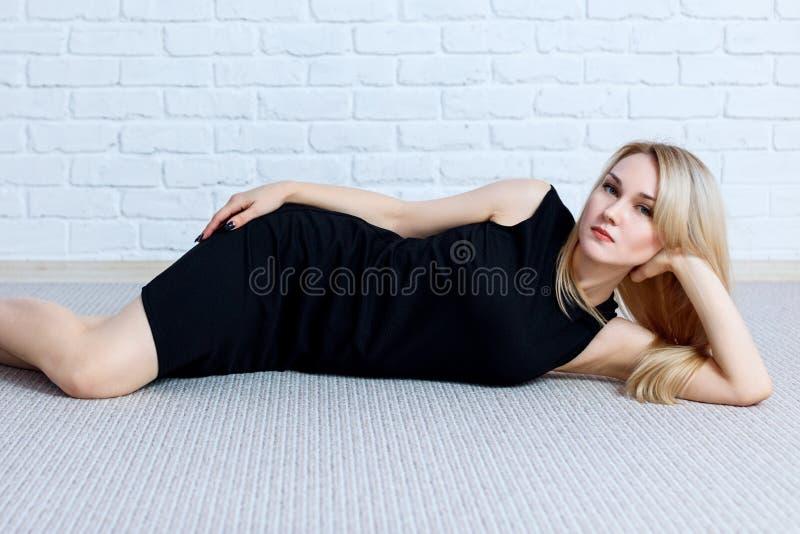 Het jonge vrouw stellen bij de vloer in studio over bakstenen muurachtergrond royalty-vrije stock foto's