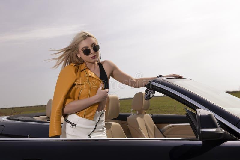 Het jonge vrouw stellen die op convertibele auto leunen stock afbeelding