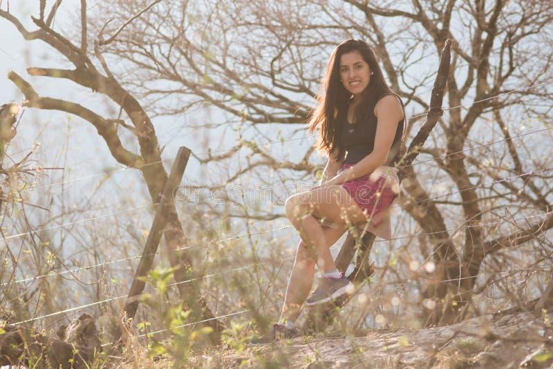 Het jonge vrouw stellen in een zonnig landschap stock fotografie