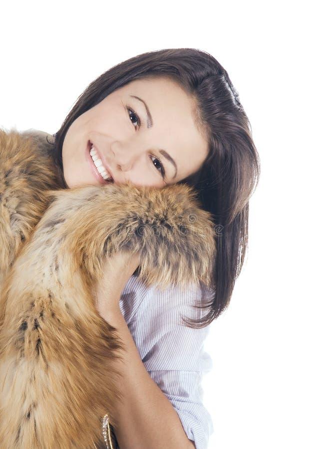 Het jonge vrouw stellen met een bont stock foto