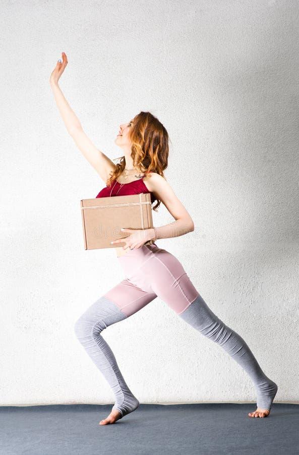 Het jonge vrouw stellen met een doos in haar handen Pakket voor yogaklassen royalty-vrije stock foto's