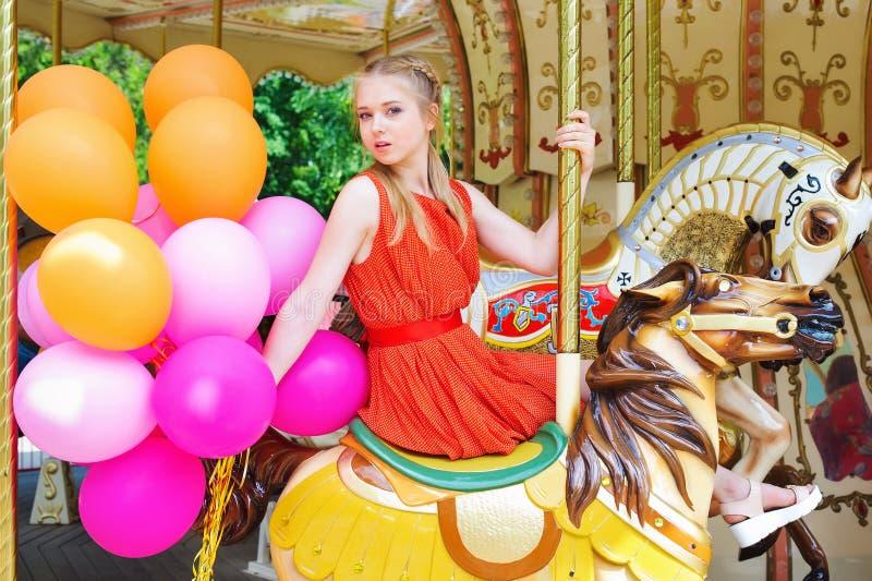 Het jonge vrouw stellen op een carrousel stock foto's