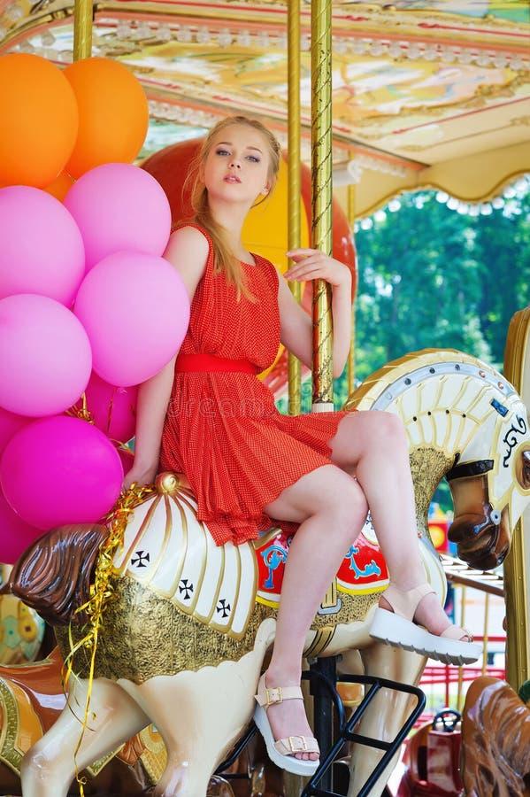Het jonge vrouw stellen op een carrousel royalty-vrije stock afbeelding