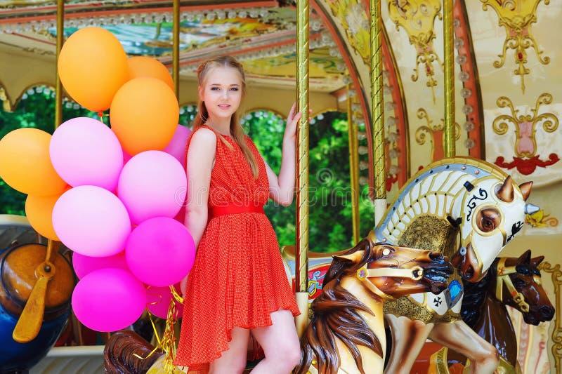 Het jonge vrouw stellen op een carrousel stock fotografie