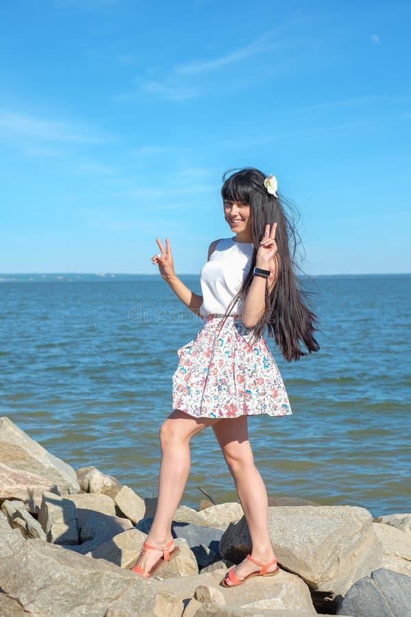 Het jonge vrouw stellen tegen het overzees stock foto