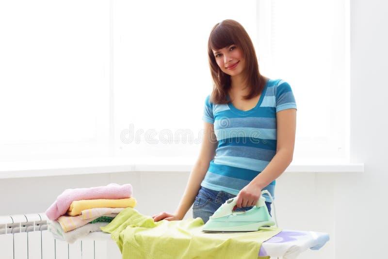 Het jonge vrouw strijken stock foto