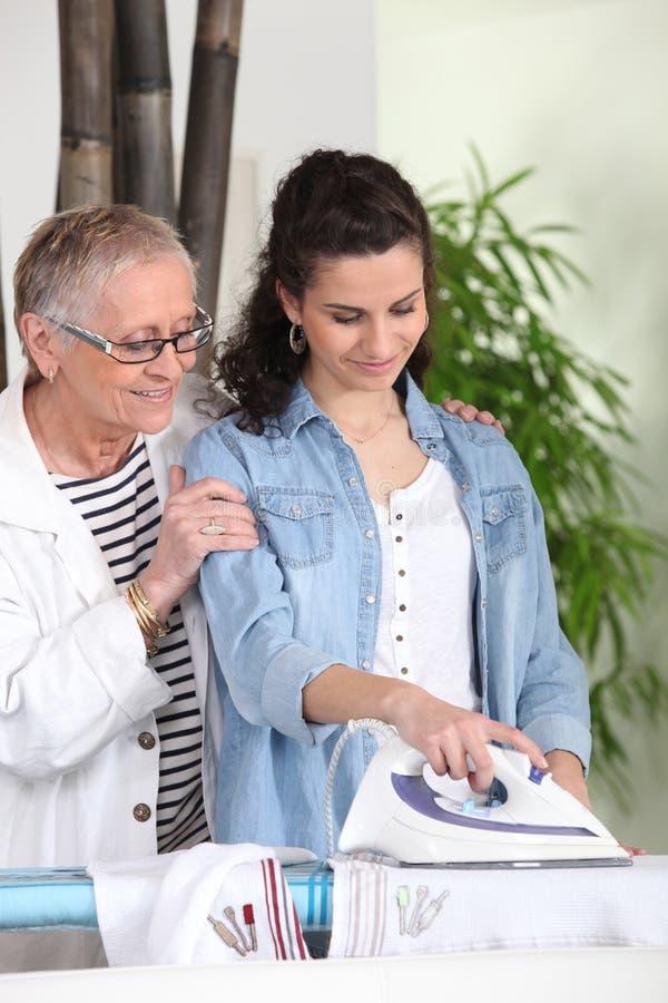 Het jonge vrouw strijken naast hogere vrouw royalty-vrije stock afbeeldingen