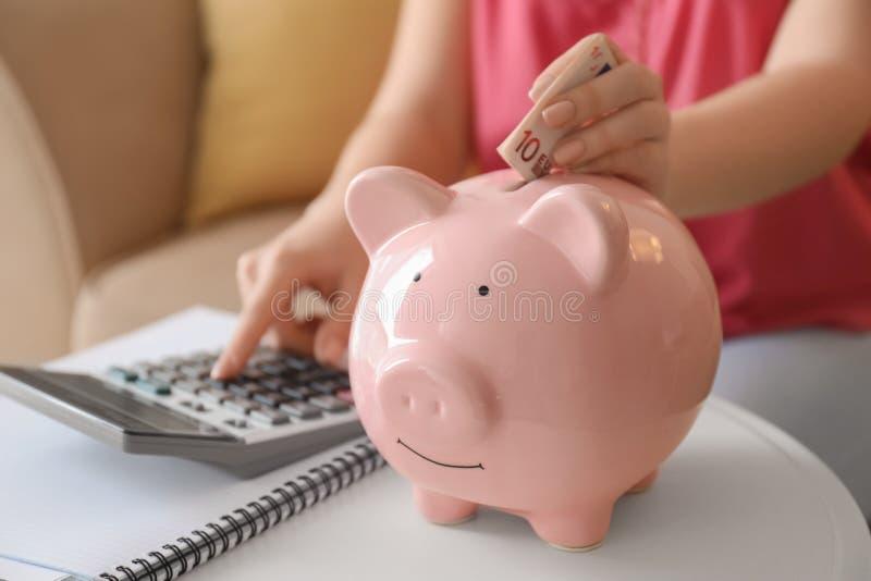 Het jonge vrouw tellen op calculator en het zetten van euro bankbiljet in spaarvarken binnen, close-up De besparingenconcept van  stock afbeeldingen