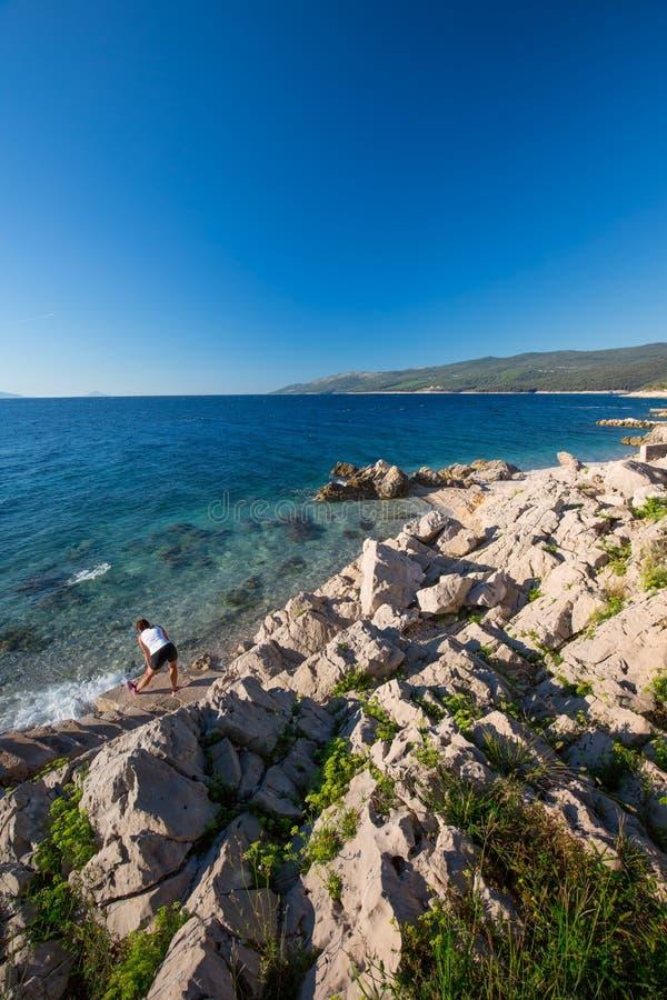 Het jonge vrouw uitoefenen door zonsopgang op de glasheldere steen tourquise overzees in Kroatië, Europa royalty-vrije stock foto's