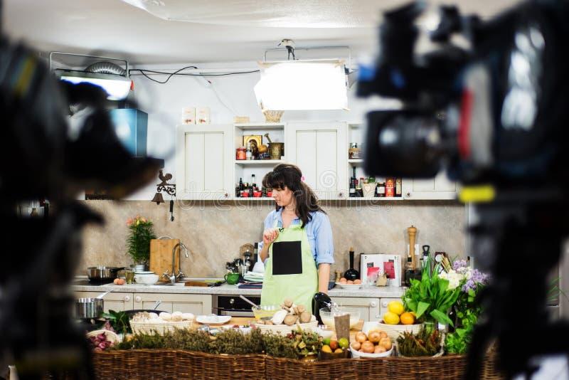 Het jonge vrouw voorbereidingen treffen voor het koken toont stock foto's
