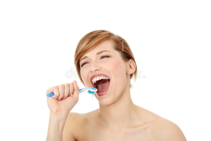 Het jonge vrouw zingen aan tandenborstel stock afbeeldingen