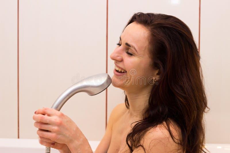 Het jonge vrouw zingen in douche stock afbeeldingen
