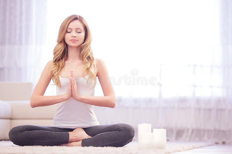 Het jonge vrouw zitting en mediteren royalty-vrije stock foto's