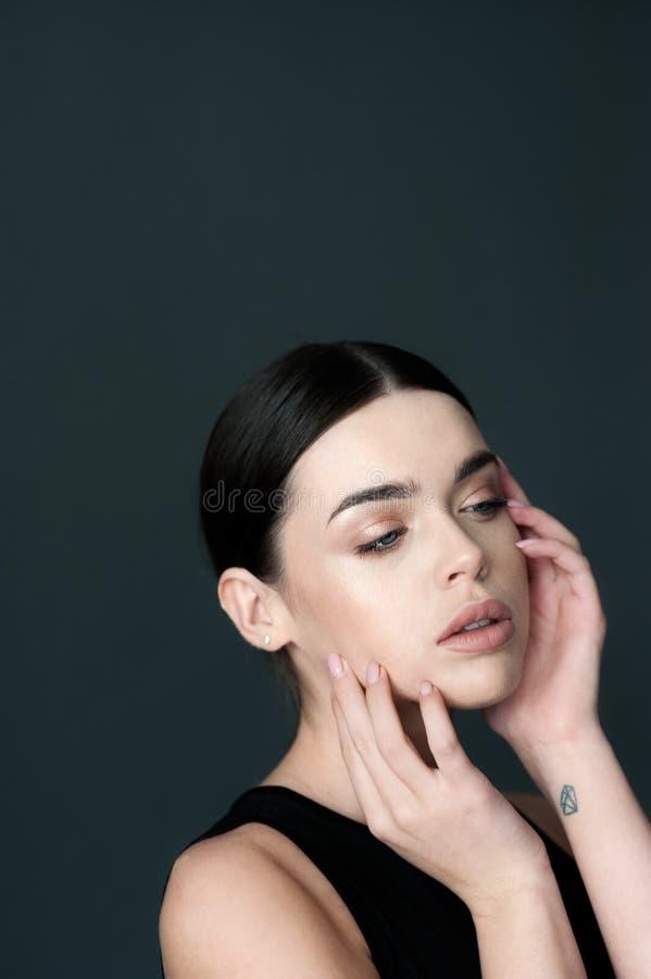 Het jonge vrouwelijke donkerbruine model van het schoonheidsportret met handen stock foto's