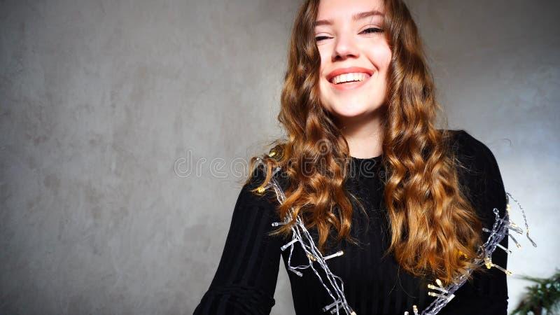 Het jonge Vrouwelijke Glimlachen, die Camera met krullend haar bekijken stock foto