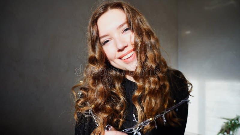 Het jonge Vrouwelijke Glimlachen, die Camera met krullend haar bekijken royalty-vrije stock afbeelding