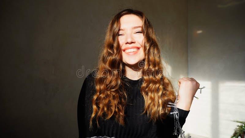 Het jonge Vrouwelijke Glimlachen, die Camera met krullend haar bekijken royalty-vrije stock foto